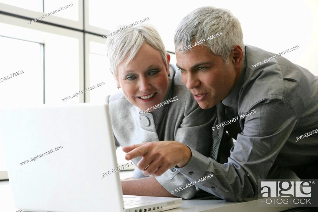 Stock Photo: Happy mature couple looking at laptop.