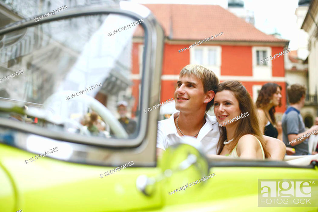 Stock Photo: Young couple sitting in a car.