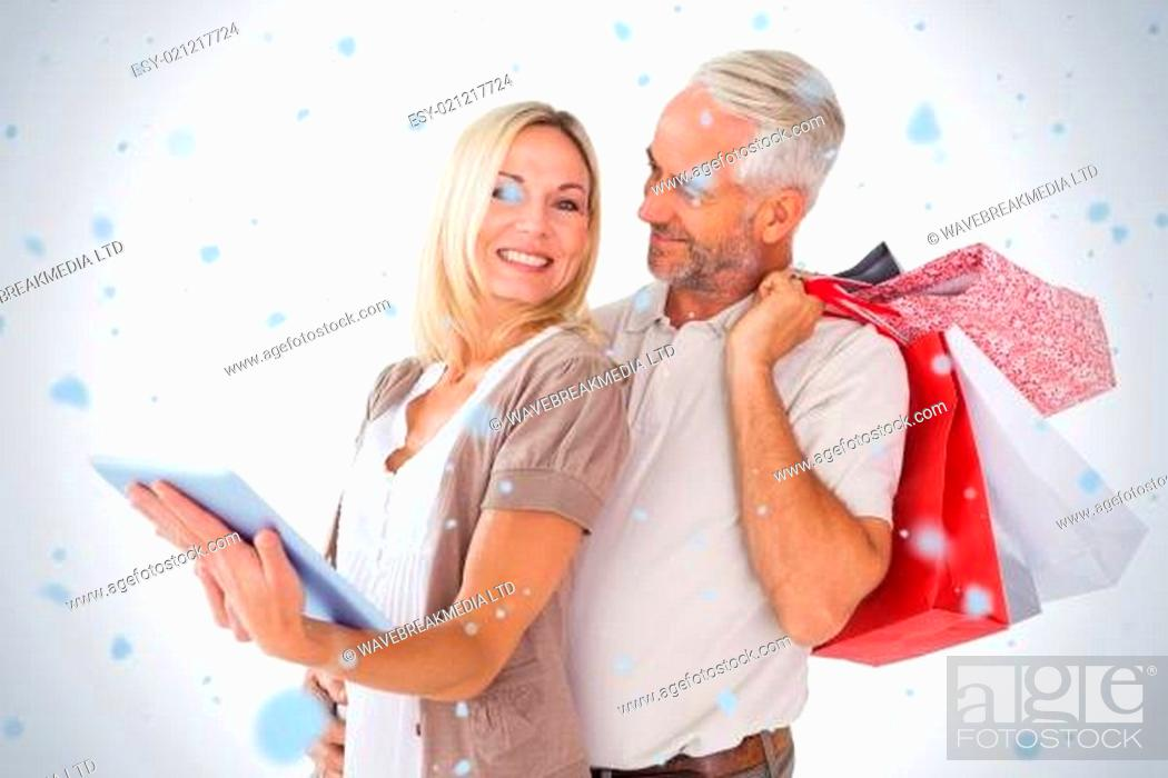 Stock Photo: Happy couple holding shopping bags and looking at tablet pc.