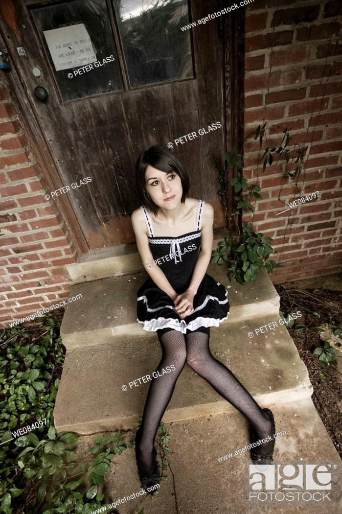 Stock Photo: Young woman, wearing fishnet stockings, sitting on concrete steps.