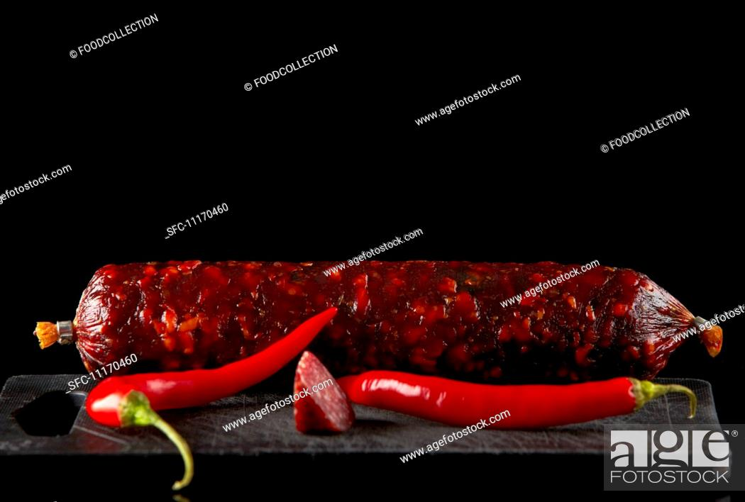 Stock Photo: Salami sausage and chili on old black plastic cutting board.