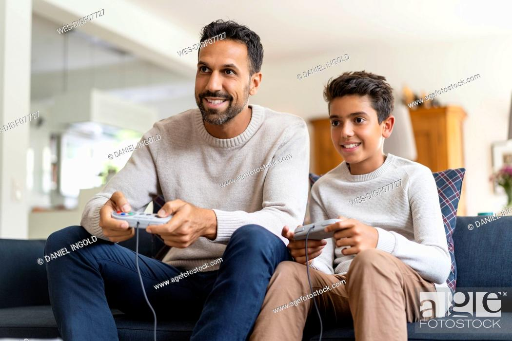 Stock Photo: Happy father and son playing video game on couch in living room.