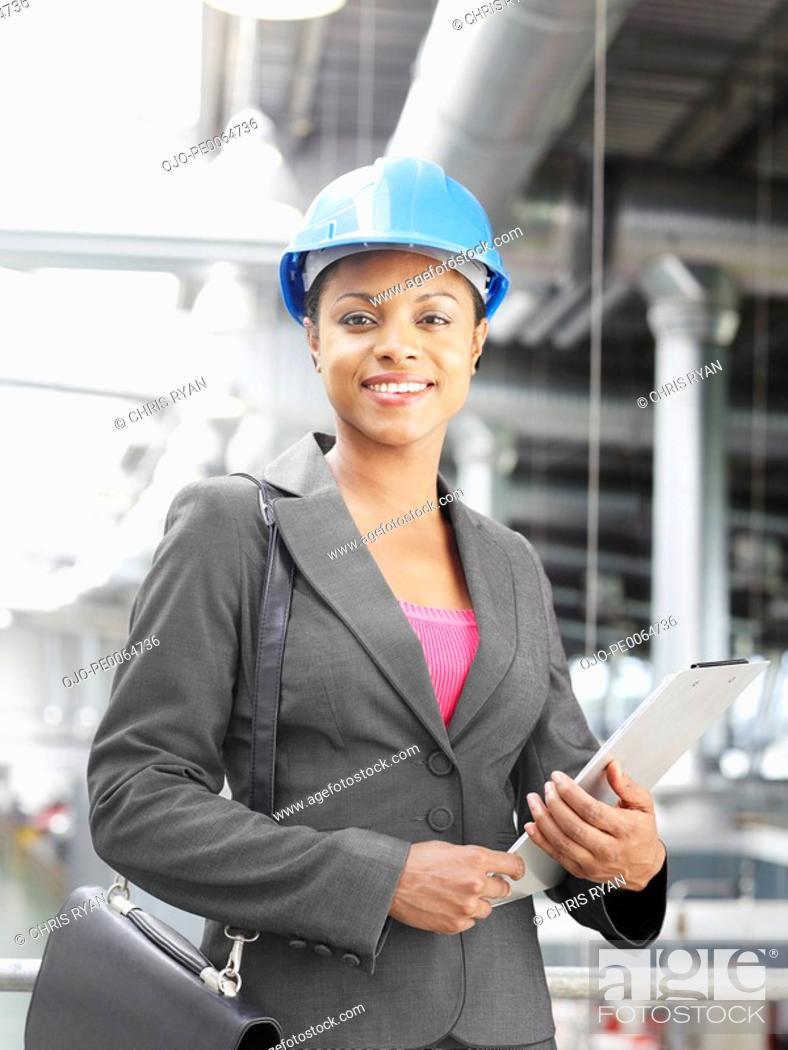 Stock Photo: Businesswoman wearing hard-hat in warehouse.