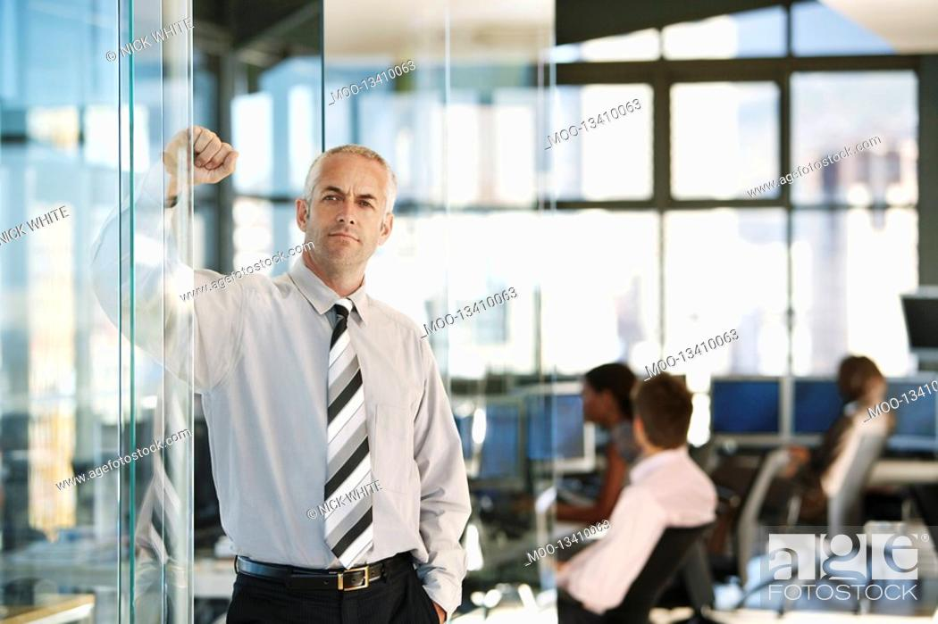 Stock Photo: Businessman leaning on door in office with office workers in background.