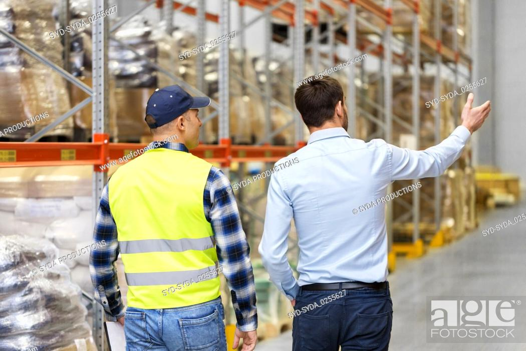 Stock Photo: businessman showing warehouse to worker.