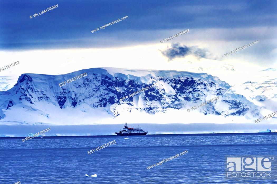 Imagen: Tourist Ship Snow Mountains Glaciers Charlotte Bay Antarctic Peninsula Antarctica. Glacier ice blue because air squeezed out of snow.