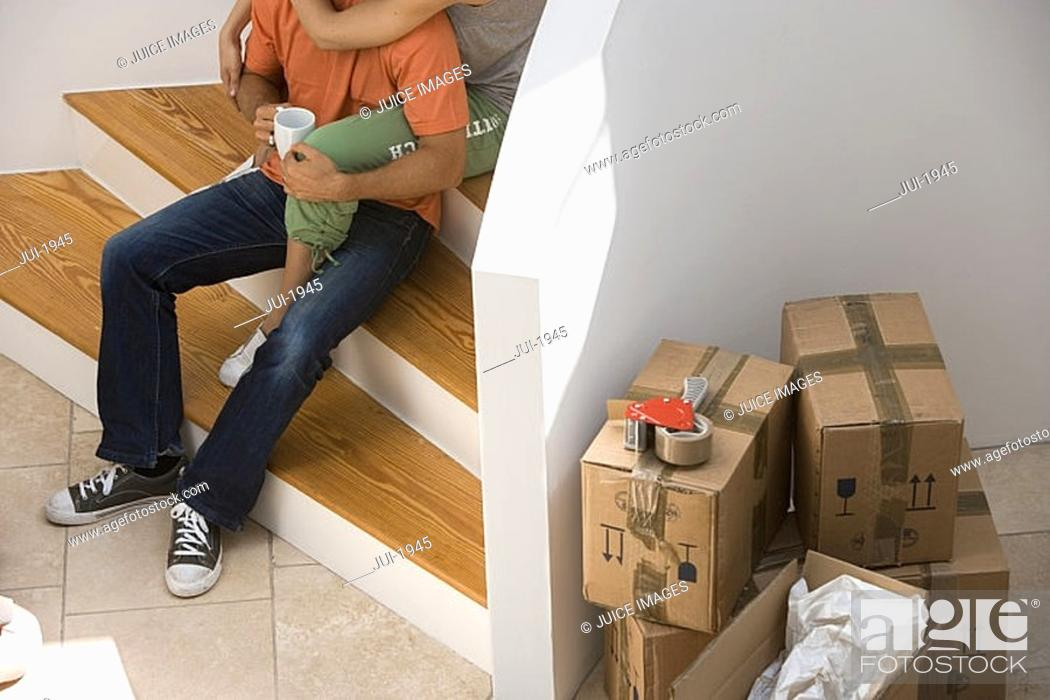 Stock Photo: Couple sitting at bottom of staircase at home, stack of packed boxes beside wall, low section.