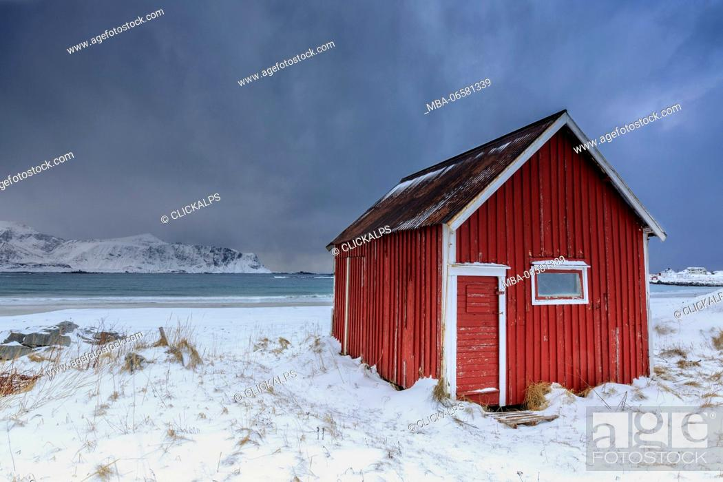 Stock Photo: A typical house of the fishermen called rorbu on the snowy beach frames the icy sea at Ramberg Lofoten Islands Norway Europe.