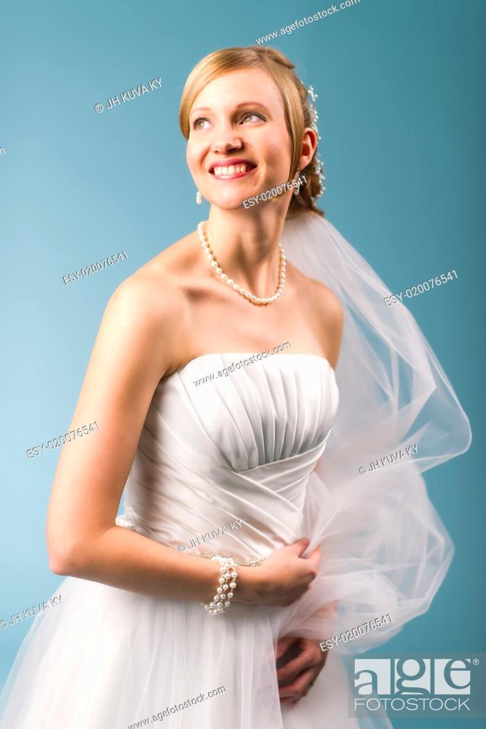 Stock Photo: Beautiful bride wearing white wedding dress, blue background.