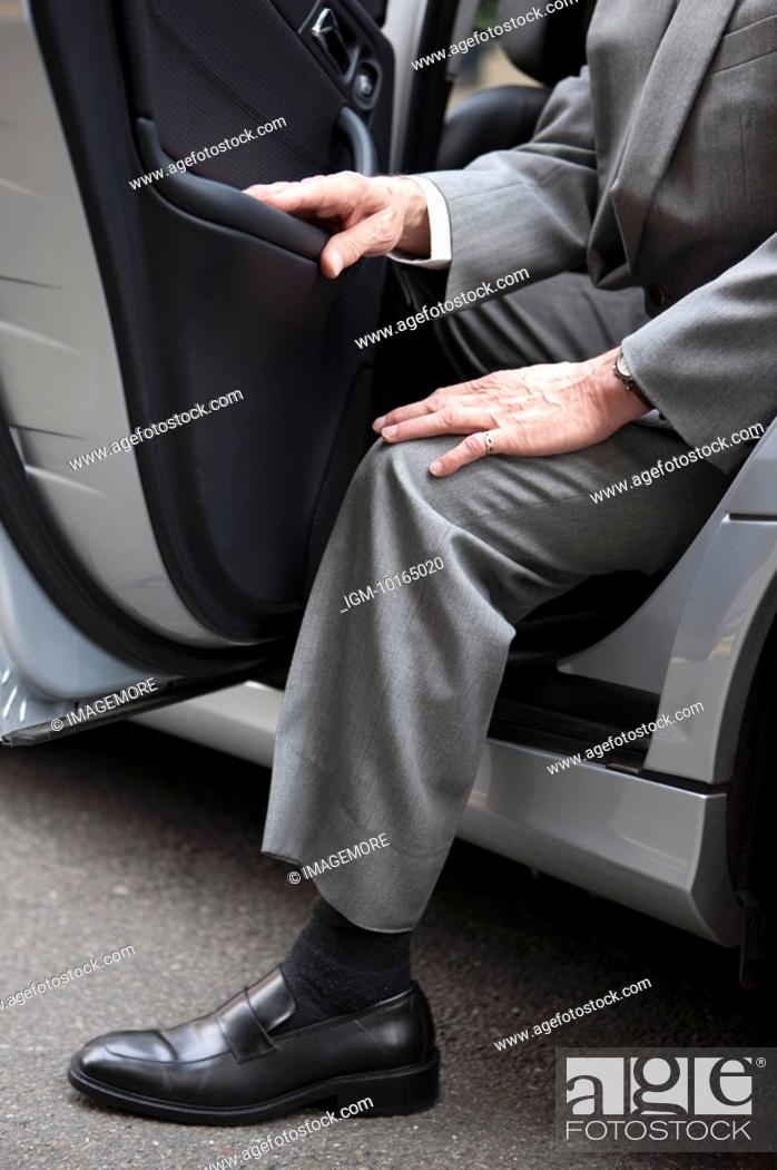 Stock Photo: Senior businessman getting down of the car.