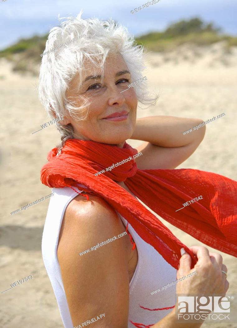 Stock Photo: Mature woman in a white suit enjoying an afternoon on the Islantilla beach, Huelva.