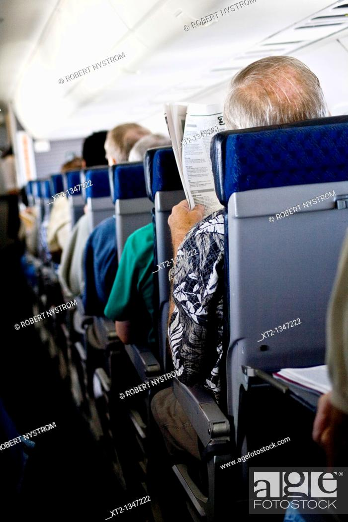 Stock Photo: An elderly man sits on an airplane and reads a newspaper.