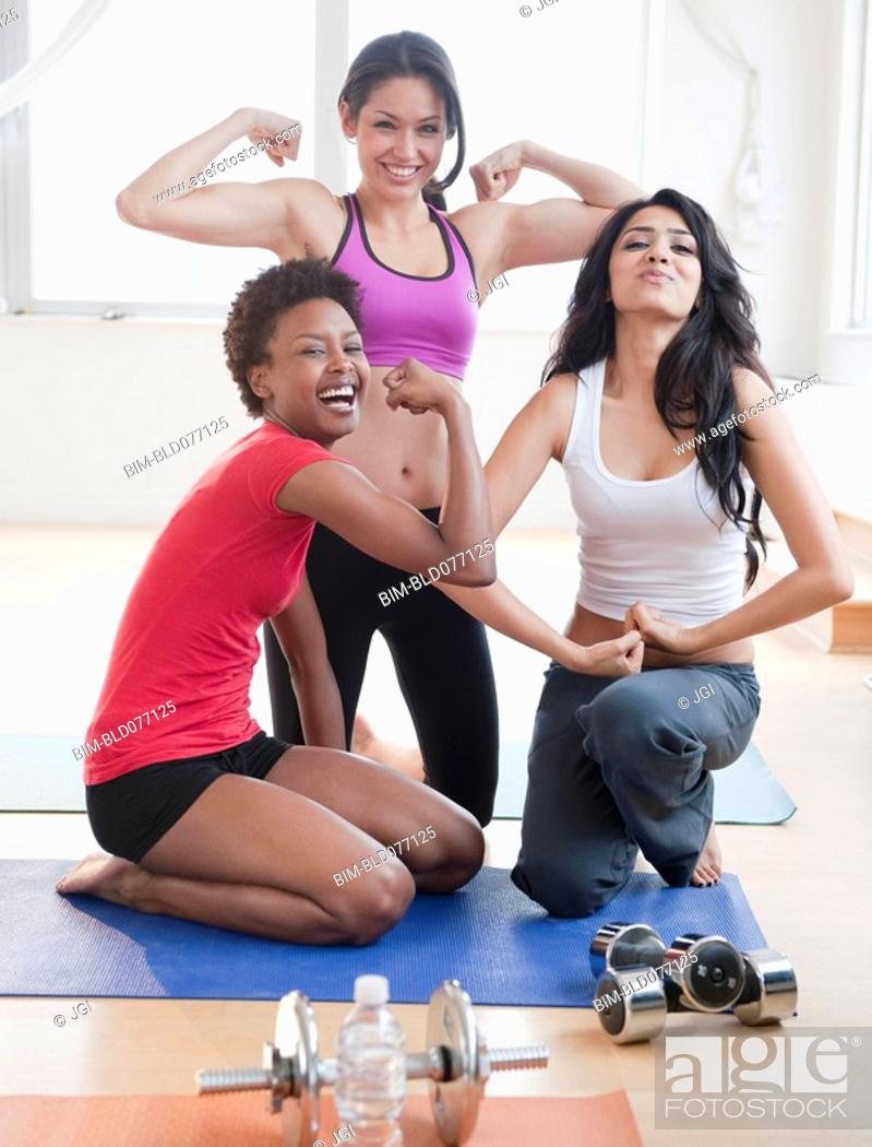 Stock Photo: Friends flexing muscles in health club.