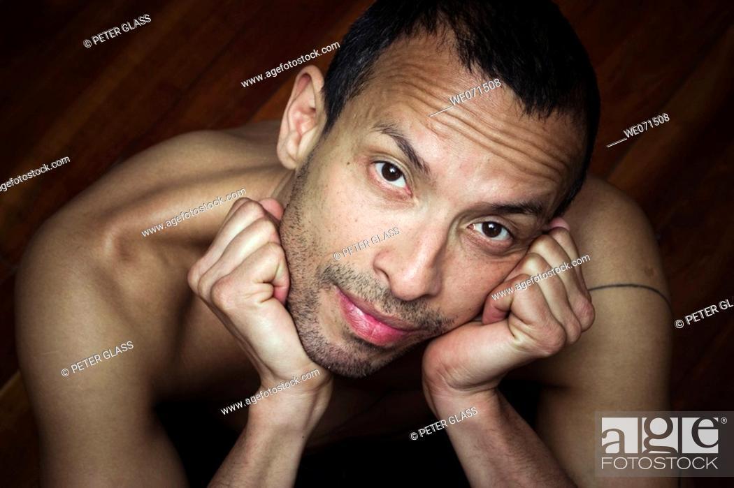 Stock Photo: Hispanic man, sitting on a wood floor, posing without a shirt.