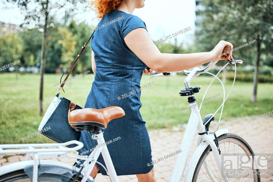 Imagen: Young woman walking in park, pushing bicycle.
