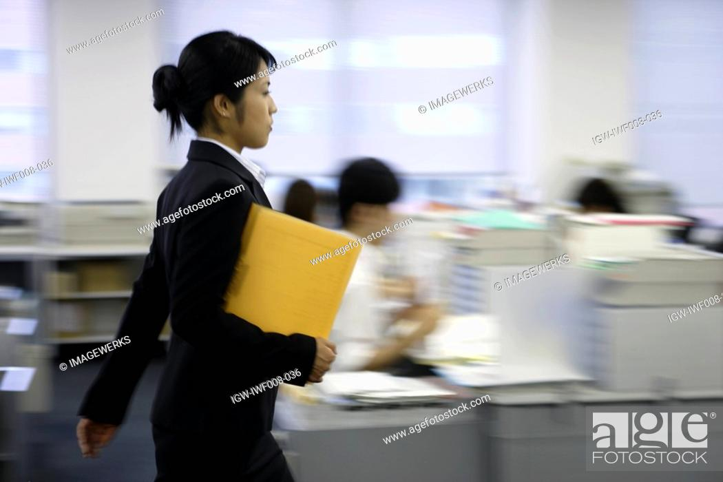 Stock Photo: A side view of a woman holding a file moves on in the office.
