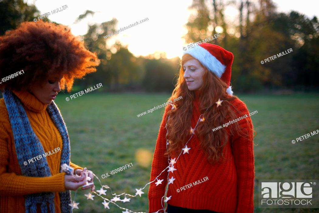 Stock Photo: Two young women, in rural setting, young woman wrapped in fairy lights.