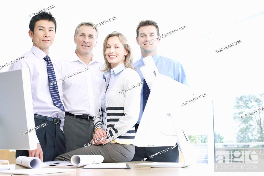 Stock Photo: Businesspeople smiling at desk.