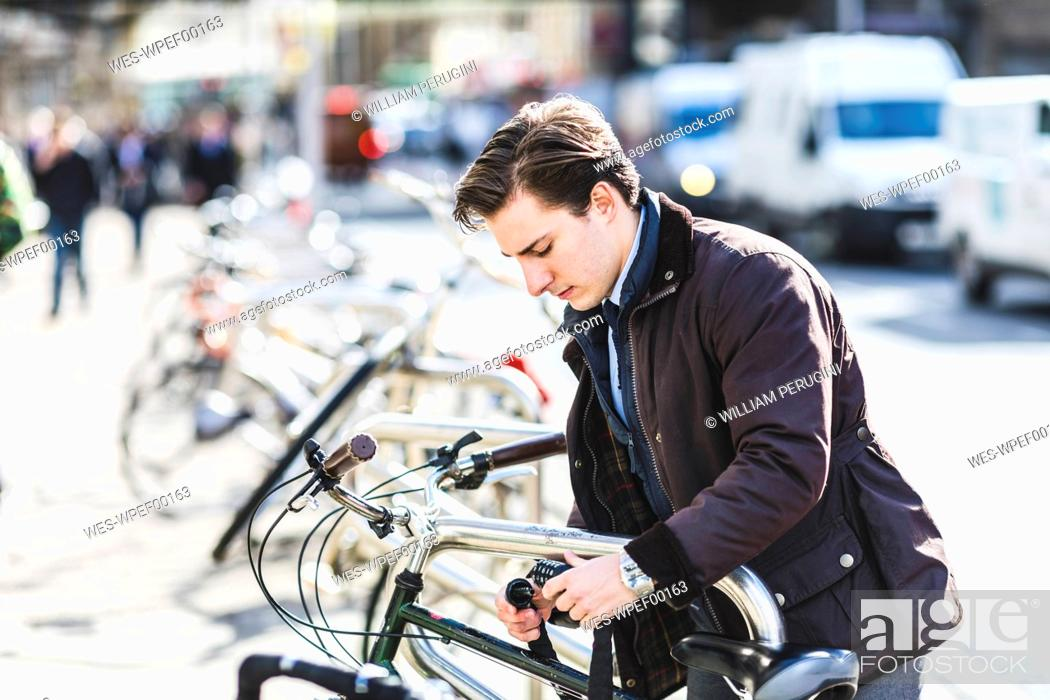 Photo de stock: Businessman locking bicycle in the city.