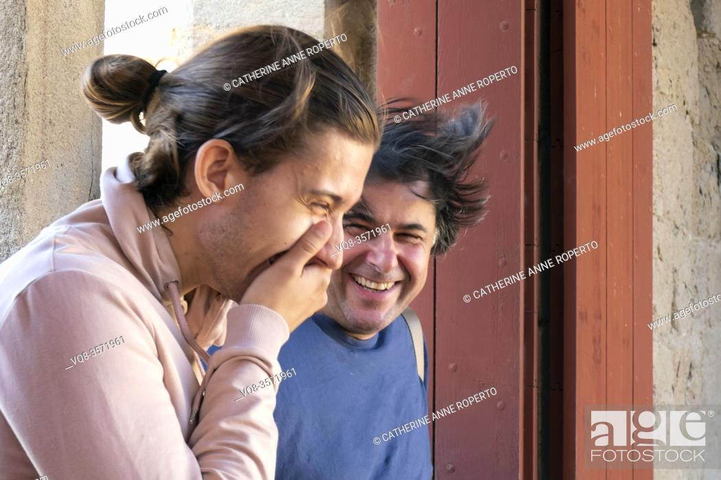 Stock Photo: Uncontrollable laughter in a hilarious moment shared between two male friends on the ramparts of Carcassonne Citadel; Occitanie; France.