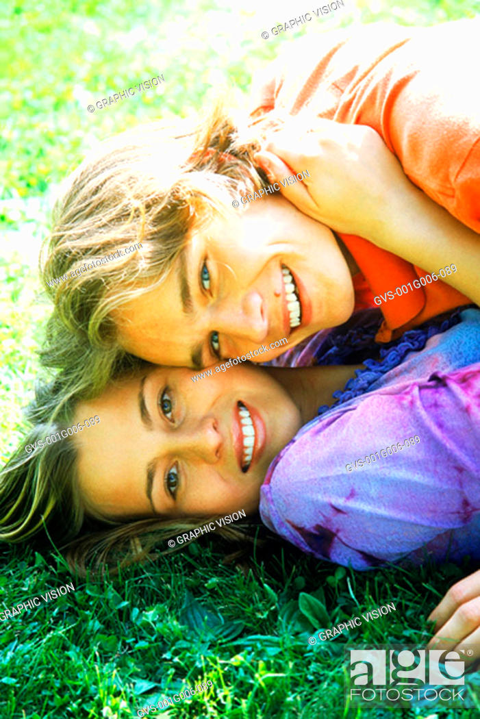 Stock Photo: Portrait of young couple lying together on the grass.
