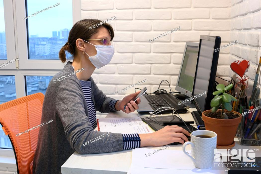 Stock Photo: A sick girl in a medical mask in self-isolation works remotely.