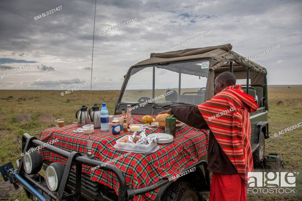 Stock Photo: Black man having picnic on hood of car in remote field.