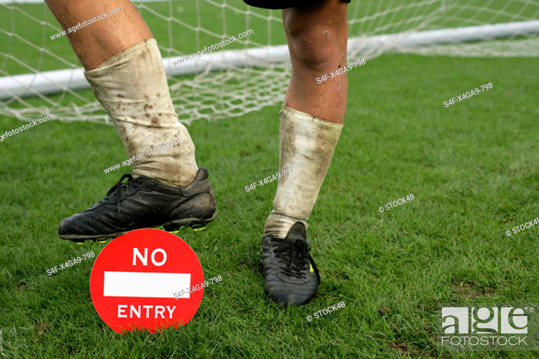 Stock Photo: Soccer player's foot on a 'no entry' label.