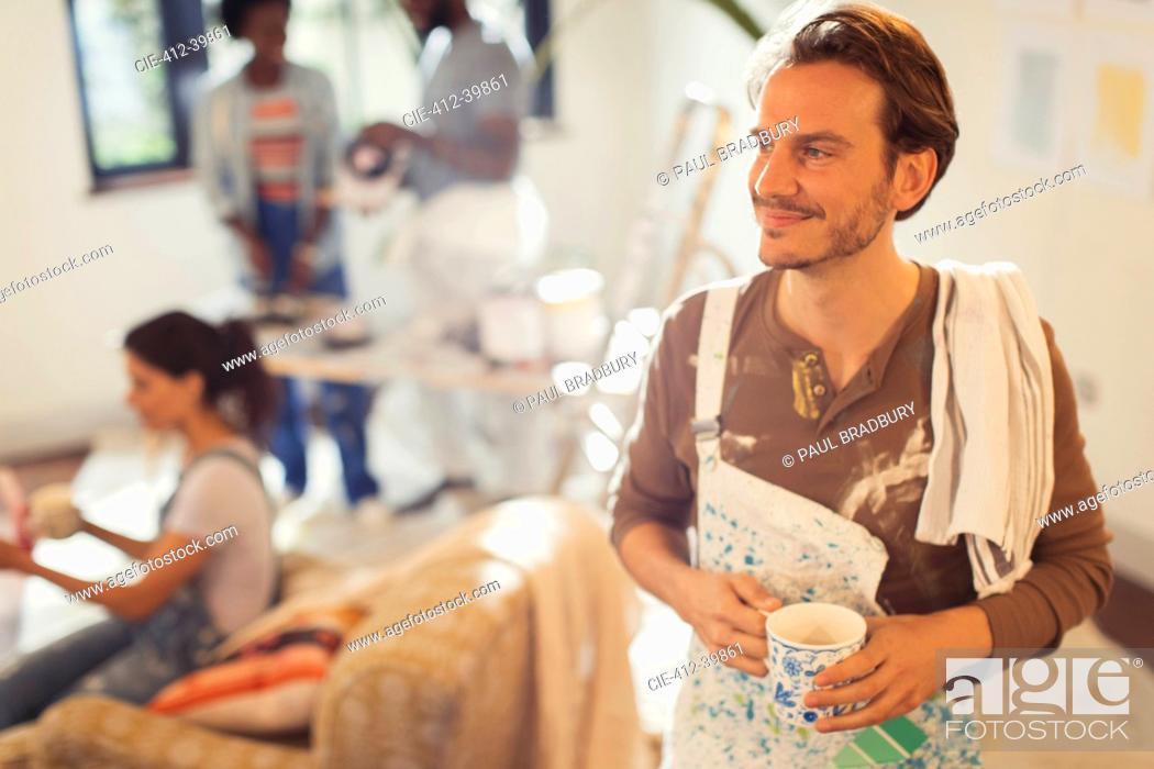 Imagen: Smiling man painting, taking coffee break.