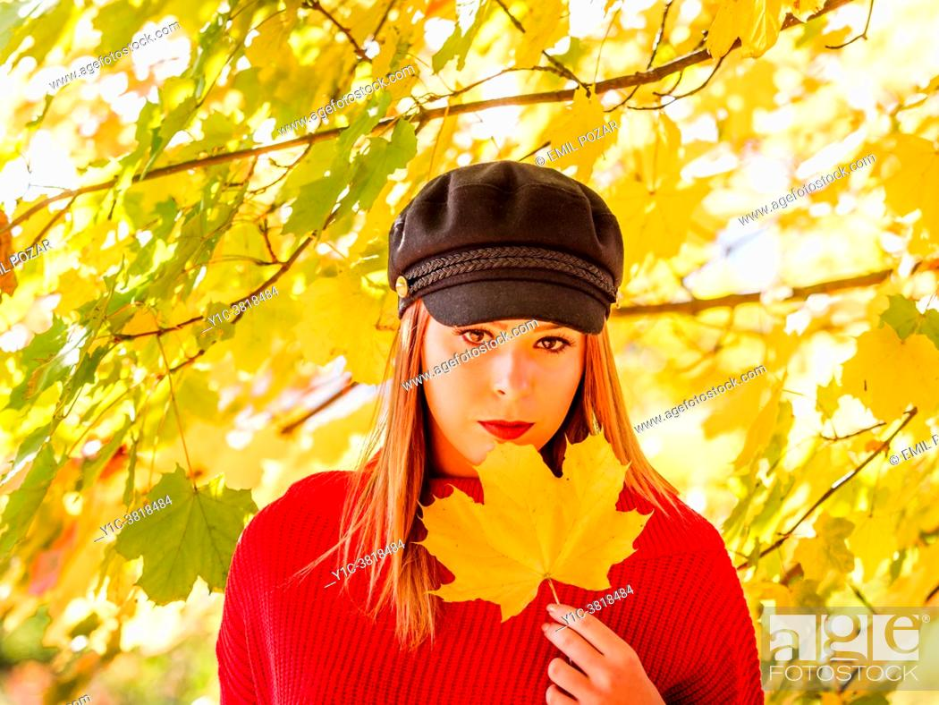 Stock Photo: Young woman is holding big leaf in hand.