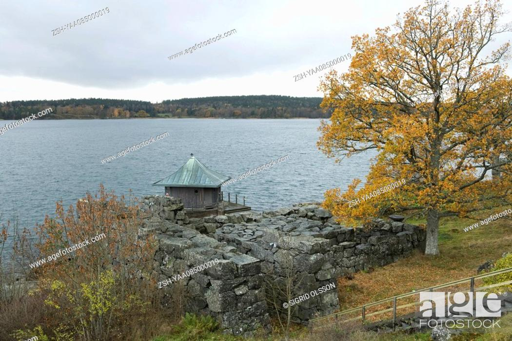 Stock Photo: Lake scene with stone wall and boathouse.