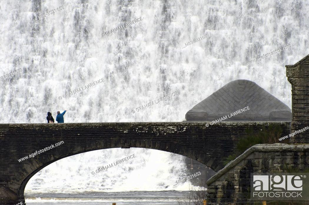 Stock Photo: A couple look at the water surging over the Caban Coch Dam in the Elan Valley, in Powys, Wales, UK.