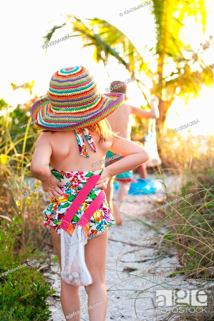 Imagen: Rear view of girl and brother collecting seashells at beach, Sanibel, Florida, USA.