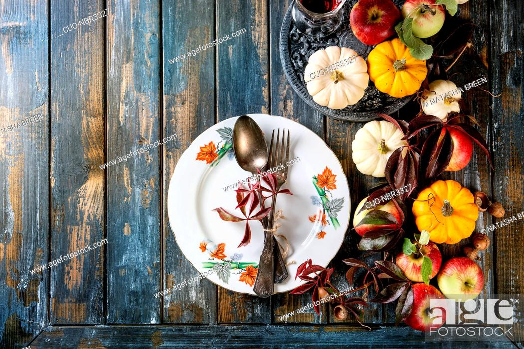 Stock Photo: Autumn holiday table decoration setting with decorative pumpkins, apples, red leaves, empty plate with vintage cutlery over wooden table.