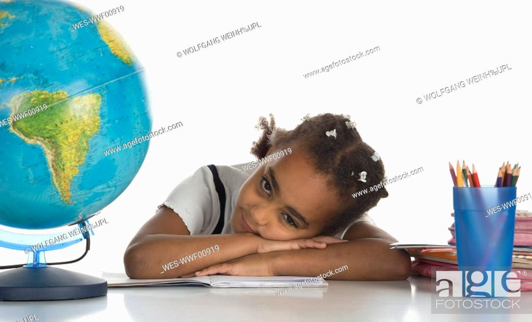 Stock Photo: African girl 6-7 with globe, portrait.
