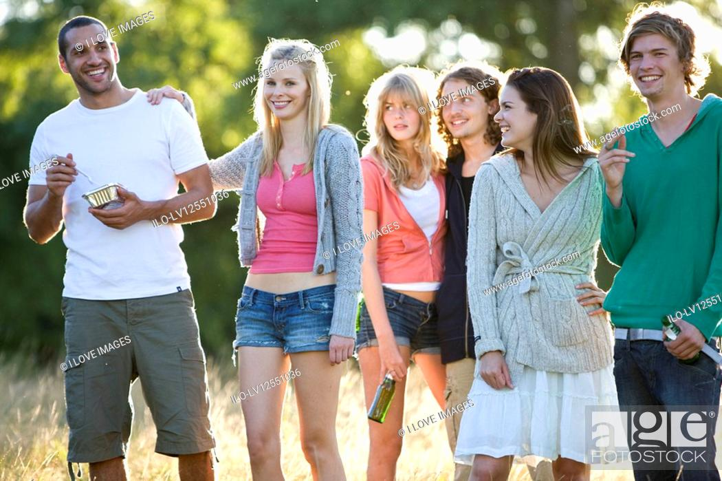 Stock Photo: A group of young friends standing in a field.
