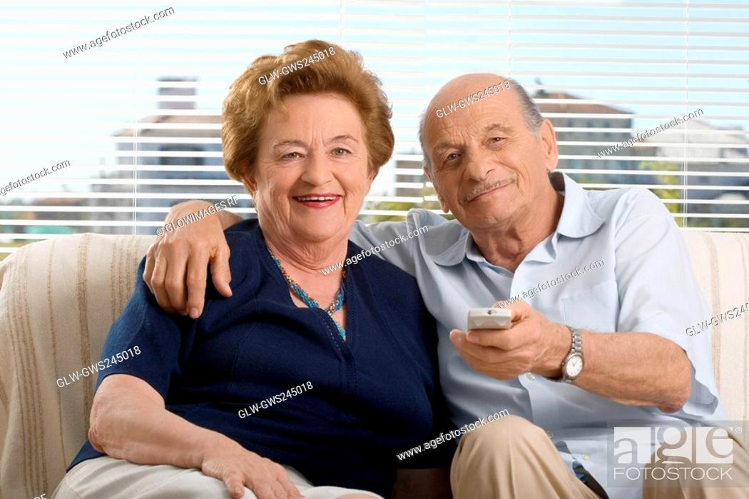 Stock Photo: Portrait of a senior couple watching television.