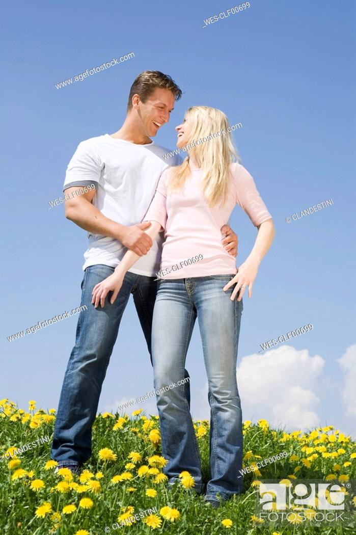 Stock Photo: Germany, Bavaria, Munich, Young couple standing in meadow, smiling, portrait.