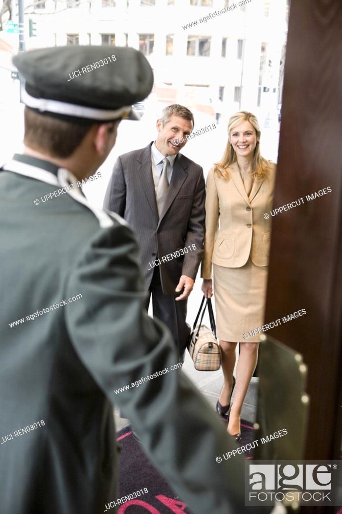 Stock Photo: Bellhop opening door for couple.