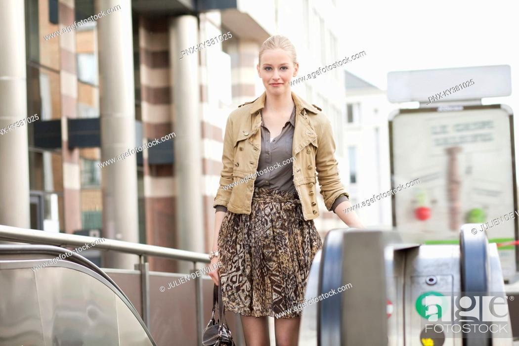 Stock Photo: Businesswoman standing on escalator.