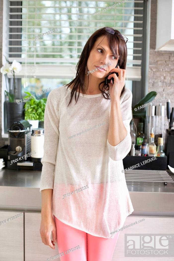 Stock Photo: Woman talking on a mobile phone in a kitchen.