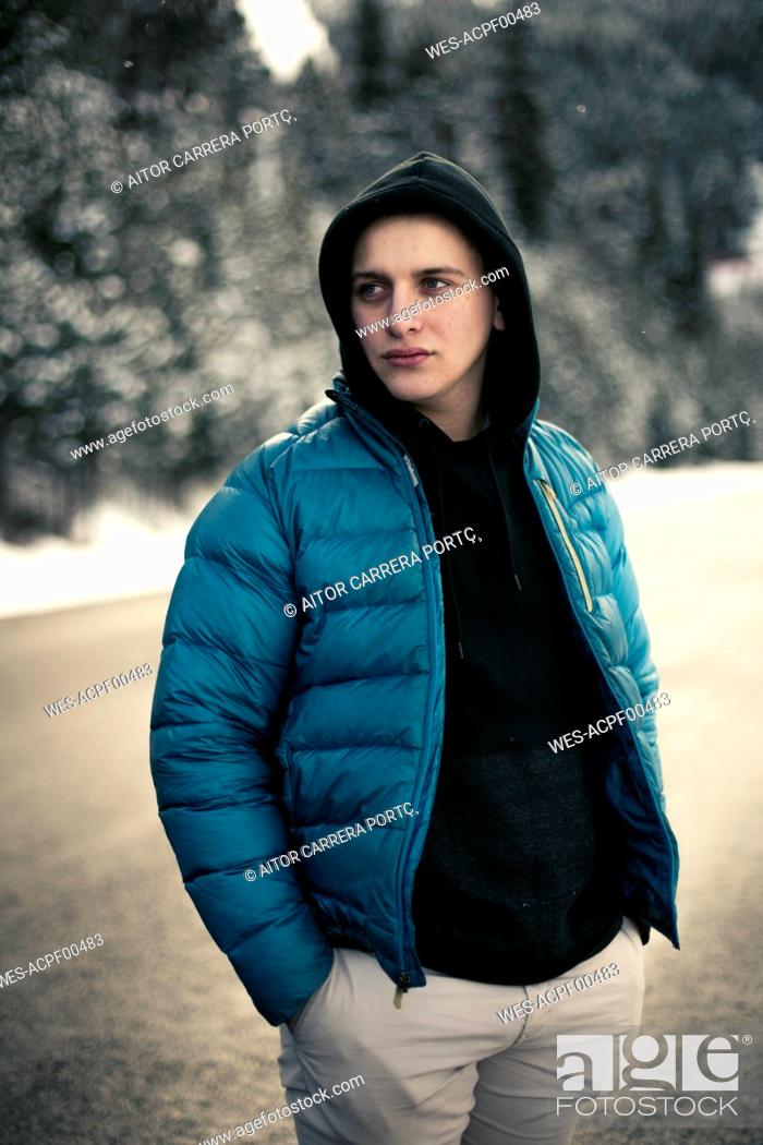 Photo de stock: Young man standing on a snowy road with trees in the background.