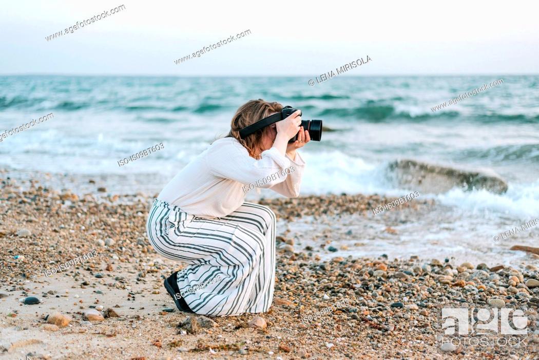 Stock Photo: Young woman taking photographs from beach, Menemsha, Martha's Vineyard, Massachusetts, USA.