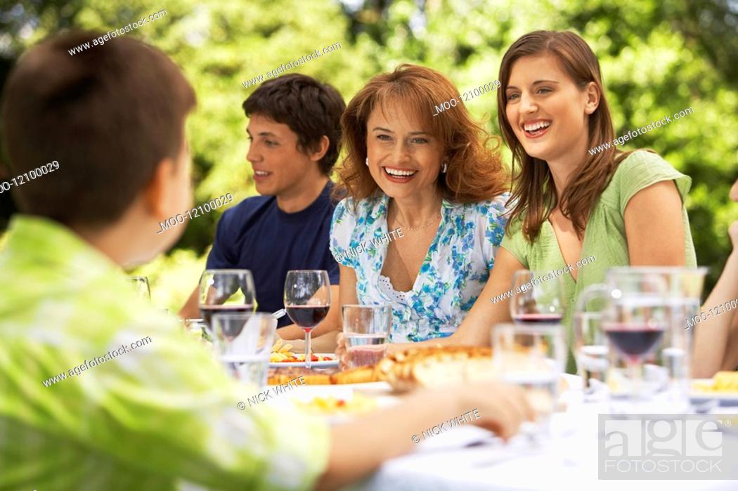 Stock Photo: Family having meal at table in back yard.