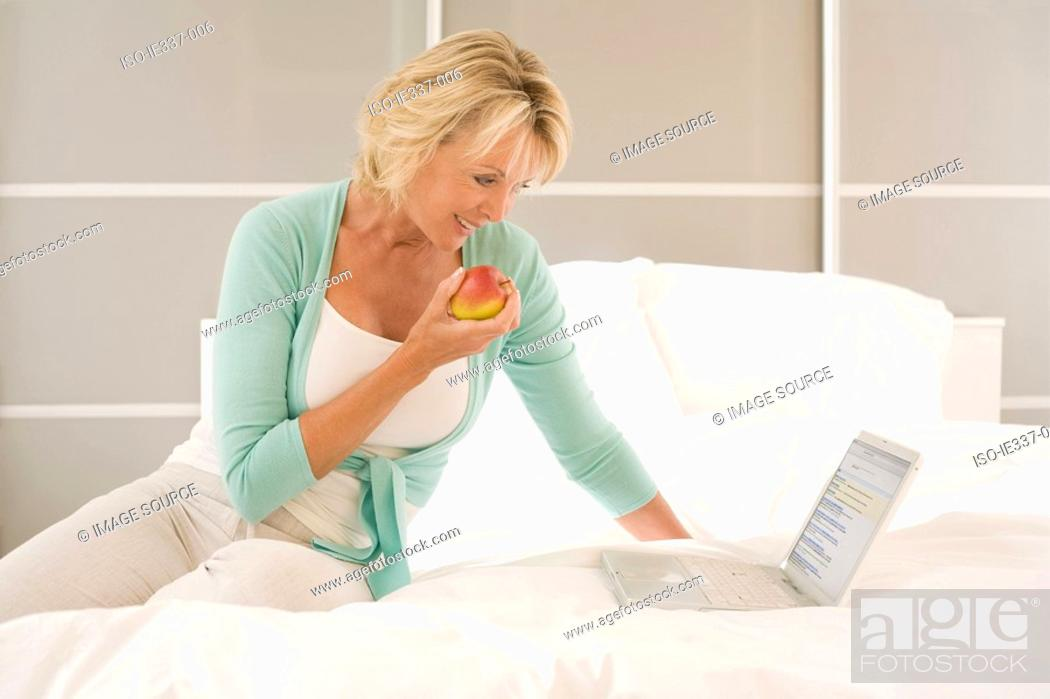 Stock Photo: Woman with apple and laptop.