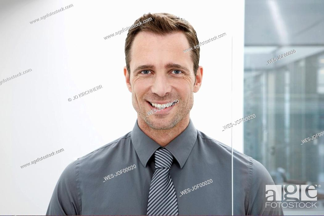 Stock Photo: Germany, Cologne, Businessman standing next glass door, smiling, portrait, close-up.