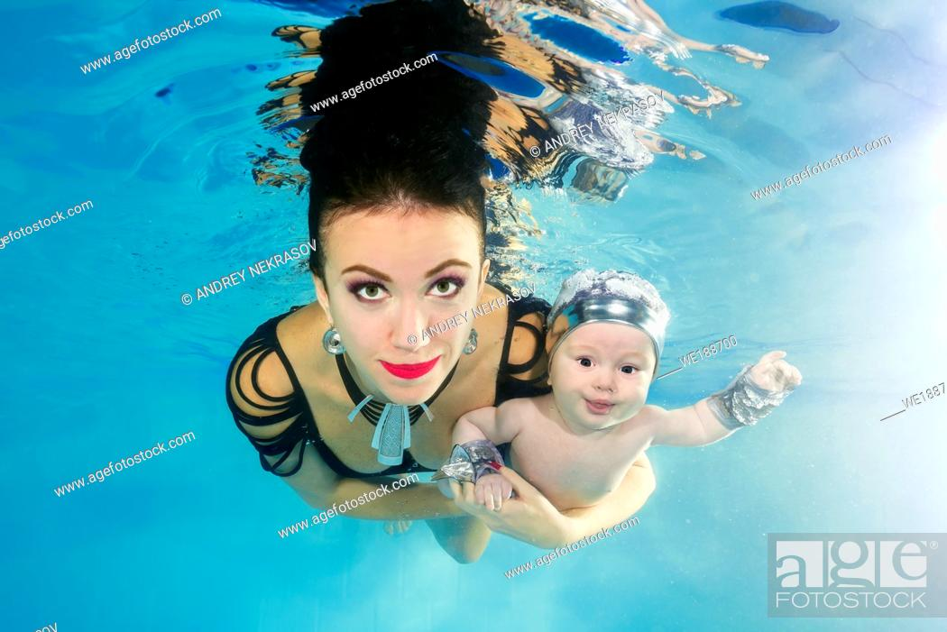 Stock Photo: Mom with a little son smiling dives underwater in a swimming pool.