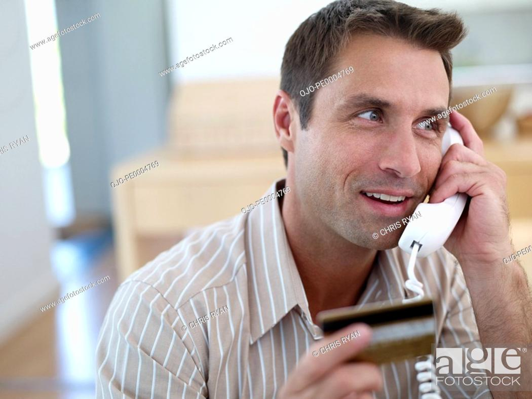 Stock Photo: Man with credit card on telephone.