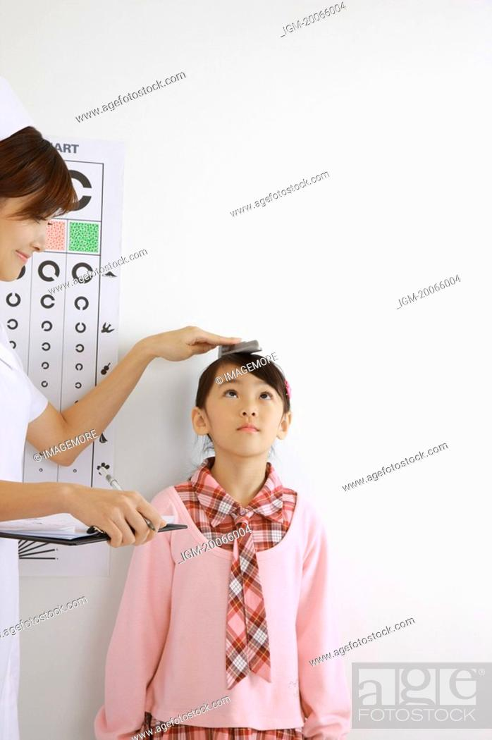 Stock Photo: Young nurse measuring little girl's height and holding clipboard.