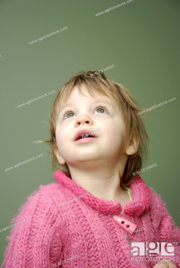 Stock Photo: A twenty month old girl looking up with an expression of interest.